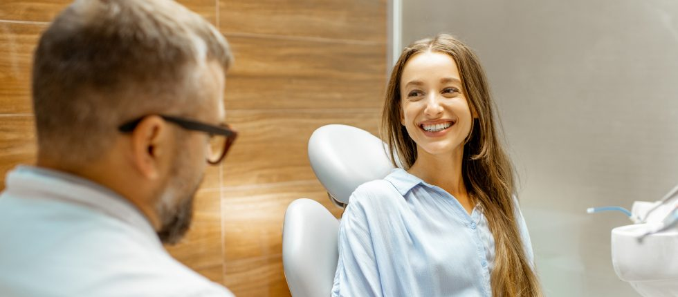 Dentist talking to smiling dental patient